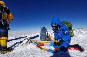 A climber kneels on the summit of Cho Oyu