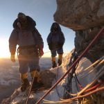 Two sherpa back lit with the morning sun on Mt Everest