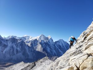 A climber traverses the granite rock of Ama Dablam