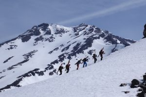 Skiers bootpacking with West Face in background
